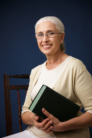 Picture of beautiful cheerful old woman sitting over dark blue background holding book. Looking camera.