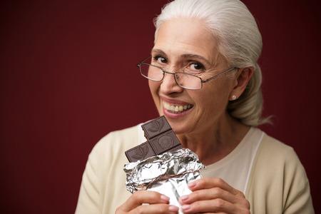 チョコレートを食べて暗い赤の背景の上に座って幸せな老婦人のイメージ。カメラを探しています。
