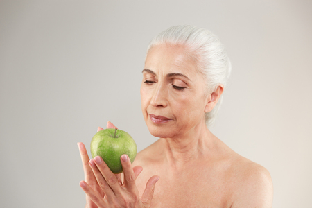 Picture of amazing naked elderly woman posing isolated over grey background. Looking aside holding apple. Stock Photo