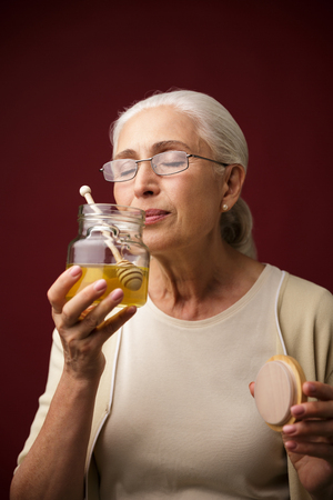 Image of old serious woman over dark red background holding honey. Eyes closed. Stock Photo