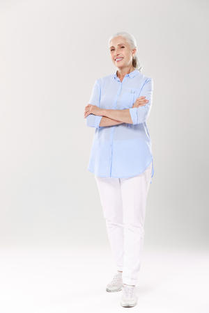Full-length portrait of charming old lady in blue shirt and white pants, standing with crossed hands, isolated on white background Фото со стока