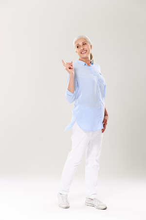 Full-length portrait of playful mature woman in blue shirt and white pants, standing and pointing with finger, looking aside, isolated on white background