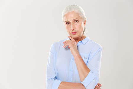 Portrait of charming serious old lady, in blue shirt, touching her chin, looking at camera, isolated over white background Stock Photo