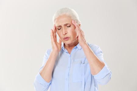 흰색 배경에 고립 된 두통을 가진 노인 숙녀 스톡 콘텐츠