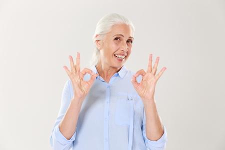Portret van glimlachende hogere vrouw in blauw overhemd die OK gebaar tonen, dat op witte achtergrond wordt geïsoleerd