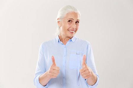 Portrait of cheerful old woman in blue shirt showing thumbs up gesture, isolated on white background Stock Photo