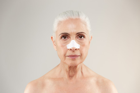 Beauty portrait of an old half naked lady with clear-up patches on her nose to remove blackhead isolated over white background Stock Photo