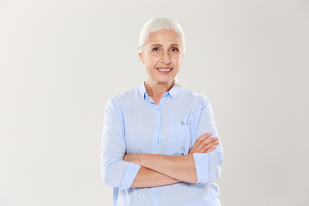 Portrait of happy elderly woman standing with crossed hands, isolated on white background