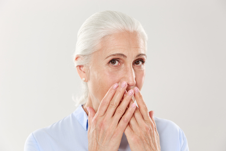 Close-up portrait of charming old lady, covering her mouth with hands, looking at camera, isolated over white background Foto de archivo