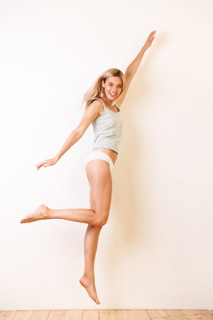 Full length portrait of a beautiful blonde girl in underwear jumping with outsretched hands over white wall background