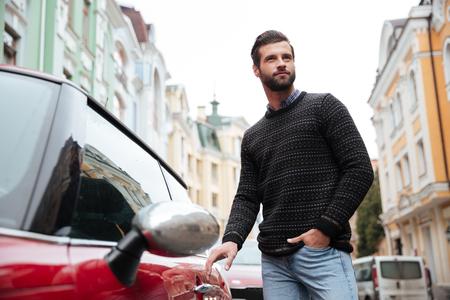 그의 차에 야외에서 점점 스웨터에 자신감이 수염 난된 남자의 초상화