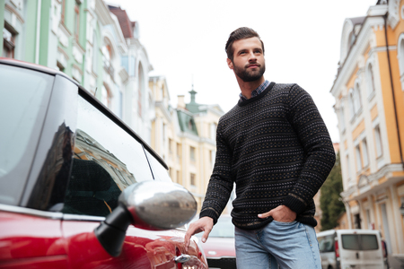 Portrait of a confident bearded man in sweater getting into his car outdoors Фото со стока