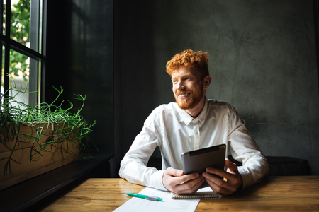 Portrait of young cheerful ginger bearded man, sitting at wooden table, holding tablet, looking at window Stock Photo