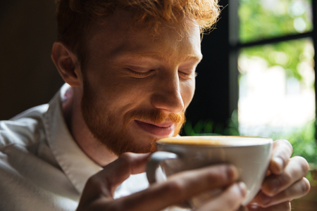 Close-up portrait of cheerful readhead bearded man sniffs coffee with closed eyes Imagens