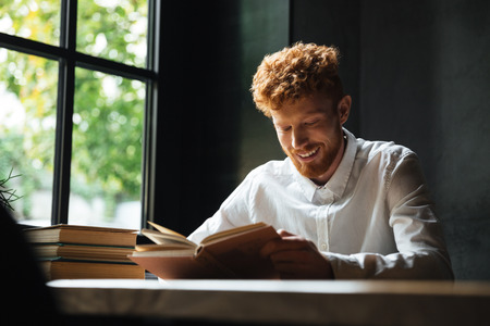 Photo of young smiling readhead bearded man in white shirt reading book