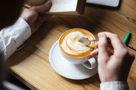 Cropped photo of man in white shirt stirring coffee while reading book