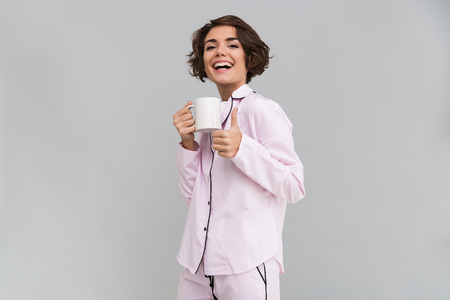nighty: Portrait of a happy cheerful girl in pajamas holding a cup and showing thumbs up gesture isolated over gray background