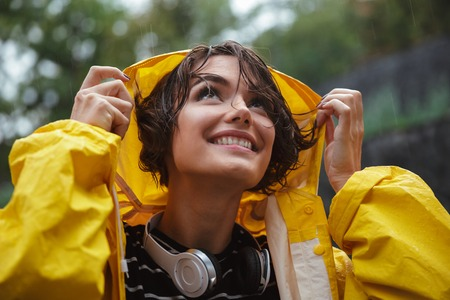 Close up portrait of a smiling pretty teenage girl with headphones wearing raincoat outdoors