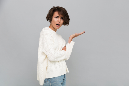 Portrait of a confused frustrated girl in sweater pointing away and looking at camera isolated over gray background Stock Photo - 88988920
