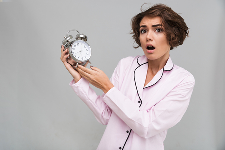 Portrait of a young scared girl in pajamas holding alarm clock and looking at camera isolated over gray background Stock Photo