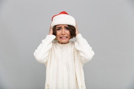 Portrait of a confused puzzled girl in christmas hat posing with hands at her head isolated over gray background