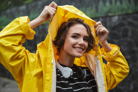 Portrait of a smiling joyful teenage girl with headphones wearing raincoat outdoors