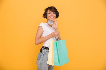 Ritratto di una ragazza allegra sorridente che tiene i sacchetti della spesa e che mostra la carta di credito mentre esaminando macchina fotografica isolata sopra fondo giallo Archivio Fotografico