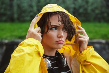 Portrait of a displeased young teenage girl wearing raincoat outdoors