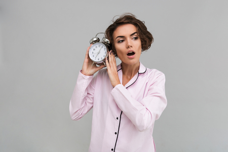 Portrait of a young shocked girl in pajamas holding alarm clock and looking away isolated over gray background Stock Photo