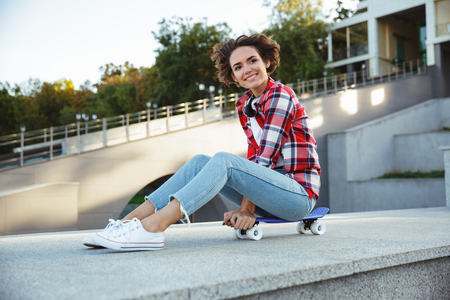 Cheerful young teenage girl sitting on a skateboard and looking away outdoors