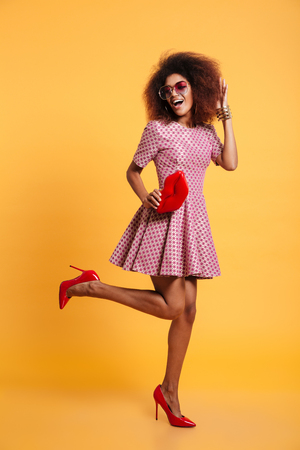 Full length photo of pretty african retro stylish woman in dress and high heels posing with big red lips, isolated on yellow background
