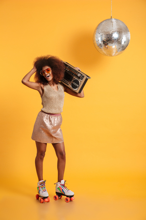 Full length portrait of charming african woman in retro clothes standing on roller skates, holding boombox, touching her afro hairstyle, looking at camera, isolated on yellow background Stock Photo