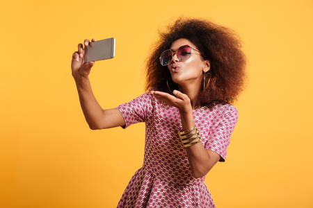 Portrait of a pretty young afro american woman in retro style clothes sending air kiss while standing and taking a selfie isolated over yellow background Stockfoto