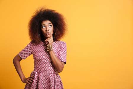 Close-up portrait of retro stylish african thinking wooman touching her face, looking aside, isolated on yellow background