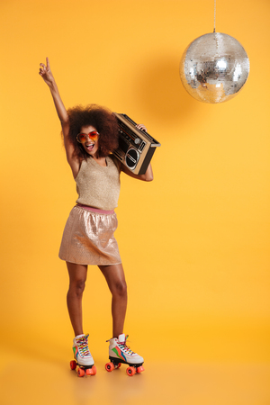 Full length portrait of happy afro american disco woman in sunglasses pointing with finger upward, standing on roller skates, holding boombox, looking at camera, isolated on yellow background