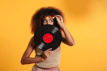 Portrait of a pretty funny afro american woman dressed in retro clothes hiding behind vinyl isolated over yellow background