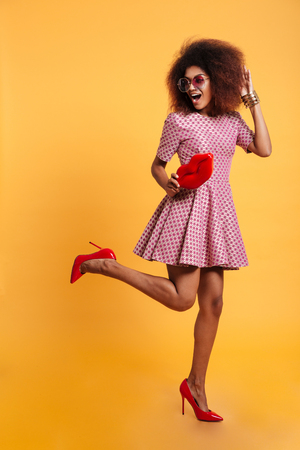 Full length photo of charming african retro stylish woman in dress and high heels standing on one leg while posing with big red lips, isolated on yellow background Stock Photo