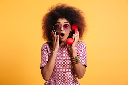 레트로 전화를 들고 afro 헤어 스타일을 가진 충격 된 복고풍 여자의 근접 사진, 카메라, 노란색 배경 위에 격리 된보고