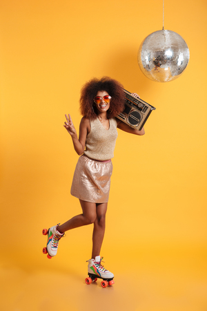 Full length portrait of smiling afro american disco woman in sunglasses showing peace gesrure, standing on roller skates, holding boombox, looking at camera, isolated on yellow background Foto de archivo
