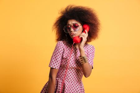 レトロな携帯電話、黄色の背景上に孤立したアフロヘアスタイルで怒っているレトロの女の子のクローズアップ写真