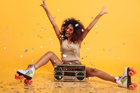 Mooie jonge Afrikaanse vrouw met afrokapsel die confettien werpen, die vredesgebaar tonen terwijl het zitten in rolschaatsen met boombox, op gele achtergrond wordt geïsoleerd