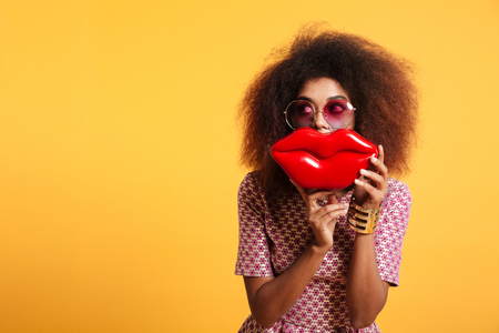 Close-up portrait of funny afro american wooman in sunglasses holding big red lips in front of her face, looking aside, isolated on yellow background
