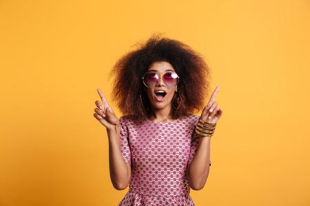 두 손가락으로 가리키는 선글라스에 레트로 세련 된 놀라 울 된 아프리카 wooman의 근접 초상화 상향 찾고 노란색 배경에 고립 된