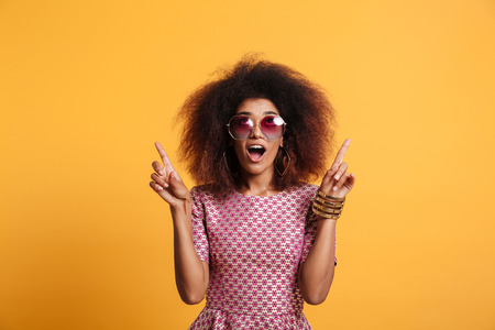 Close-up portrait of retro stylish amazed african wooman in sunglasses pointing with two fingers up, looking upward, isolated on yellow background