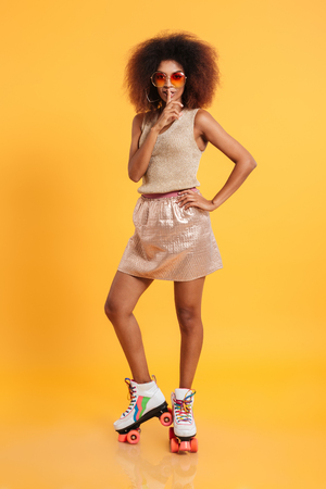 hair roller: Full length portrait of a young afro american woman dressed in retro clothes and wearing skates while standing and showing silence gesture isolated over yellow background