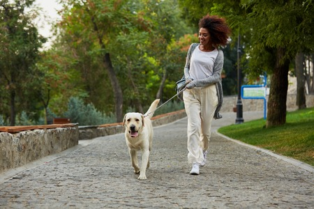 Funny healthy african lady running in the morning with her dog in park in the morning