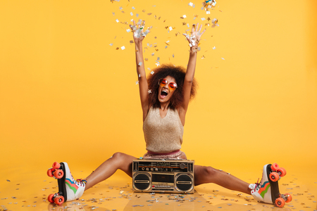 Emotional african disko woman in retro wear and roller scates throwing confetti while sitting with boombox, isolated on yellow background