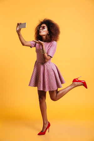 Full length portrait of a lovely afro american woman in retro style clothes sending air kiss and posing while standing and taking a selfie isolated over yellow background