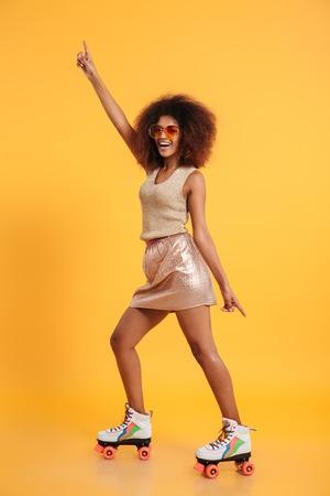 Retrato de cuerpo entero de una alegre mujer afroamericana vestida con ropa retro y con patines mientras está de pie y bailando aislado sobre fondo amarillo