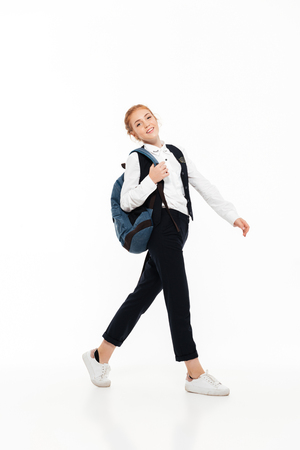 Full length image of smiling gigner student woman with backpack walking in studio and looking at the camera over white background